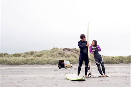 Couple on beach, woman leaning on surfboard Stock Photo - Premium Royalty-Free, Code: 649-07437750