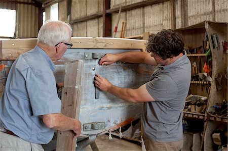 dependable - Father watching son restore boat in workshop Stock Photo - Premium Royalty-Free, Code: 649-07437817