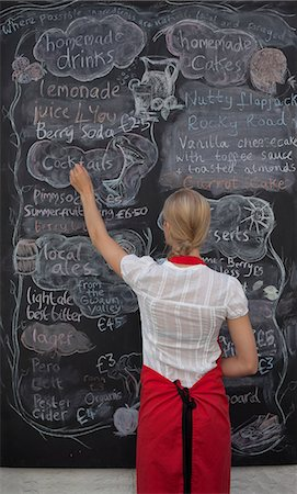 Waitress writing on blackboard menu in cafe Stock Photo - Premium Royalty-Free, Code: 649-07437827