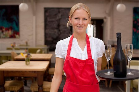 Portrait of waitress with tray of wine and glasses in cafe Stock Photo - Premium Royalty-Free, Code: 649-07437829