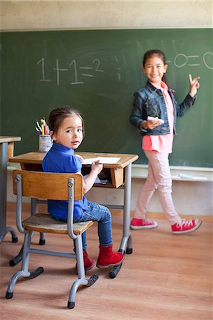 Girl by blackboard and sister at desk Stock Photo - Premium Royalty-Free, Code: 649-07437855