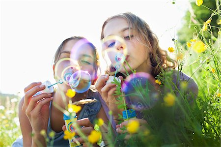 family  fun  outside - Sisters sitting in field of flower blowing bubbles Stock Photo - Premium Royalty-Free, Code: 649-07437897
