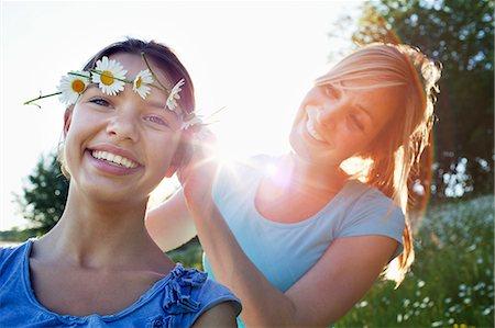 Mother tying daisy chain around daughter's head Stock Photo - Premium Royalty-Free, Code: 649-07437899