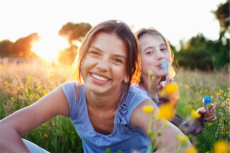 Portrait of girls sitting in field, one blowing bubbles Stock Photo - Premium Royalty-Free, Code: 649-07437906