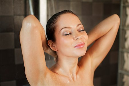 Young woman showering, eyes closed Stock Photo - Premium Royalty-Free, Code: 649-07437937