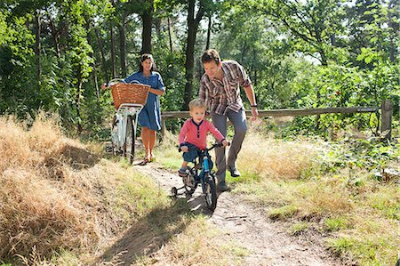 Family cycling though forest Stock Photo - Premium Royalty-Free, Code: 649-07437975