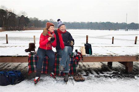 Couple sitting on pier having hot drink Stock Photo - Premium Royalty-Free, Code: 649-07437997