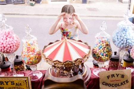 sweets - Girl looking through window of sweet shop Stock Photo - Premium Royalty-Free, Code: 649-07438037
