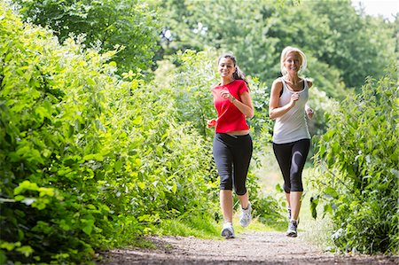 Women jogging through forest Stock Photo - Premium Royalty-Free, Code: 649-07438051