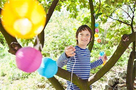 Boy putting fairy lights in tree Stock Photo - Premium Royalty-Free, Code: 649-07438090