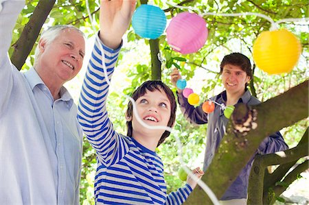 Three generation family putting fairy lights in tree Stock Photo - Premium Royalty-Free, Code: 649-07438091