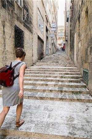 Female tourist walking up stairs, Valletta, Malta Stock Photo - Premium Royalty-Free, Code: 649-07520126