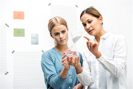 Female colleagues discussing workings of the hourglass Stock Photo - Premium Royalty-Free, Code: 649-07520123