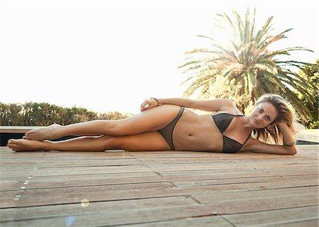 Woman in bikini lying on wooden decking Stock Photo - Premium Royalty-Free, Code: 649-07520187