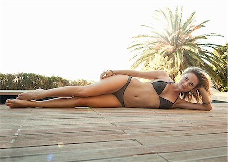 sexy black women in bikinis - Woman in bikini lying on wooden decking Stock Photo - Premium Royalty-Free, Code: 649-07520187