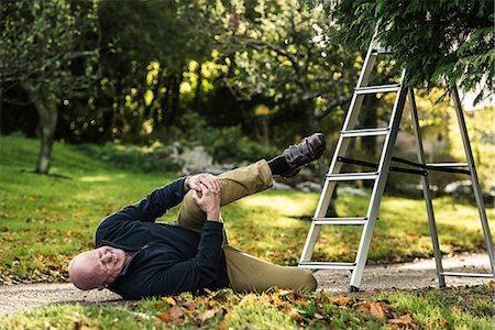 Senior man grimacing over injured knee Stock Photo - Premium Royalty-Free, Code: 649-07520209