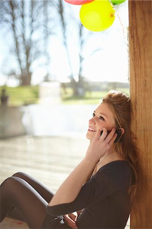 Teenage girl talking on mobile at birthday party Stock Photo - Premium Royalty-Free, Code: 649-07520273