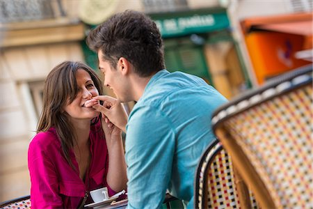 Young couple sharing macaroon at pavement cafe, Paris, France Stock Photo - Premium Royalty-Free, Code: 649-07520316