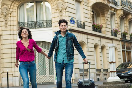 Young couple walking with wheeled suitcase, Paris, France Stock Photo - Premium Royalty-Free, Code: 649-07520319