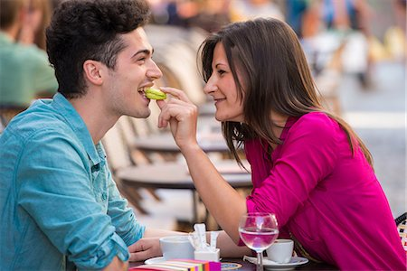 Young couple eating macaroon at pavement cafe, Paris, France Stock Photo - Premium Royalty-Free, Code: 649-07520336