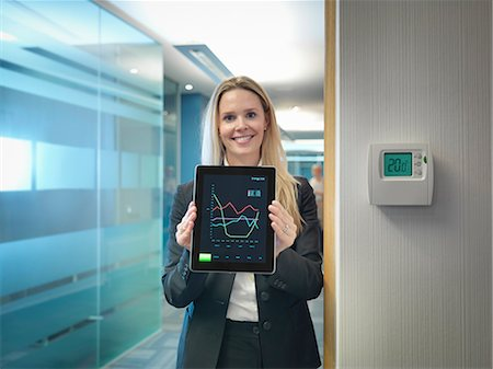 Portrait of office worker holding digital tablet next to office thermostat adjusted to make energy savings Stock Photo - Premium Royalty-Free, Code: 649-07520347