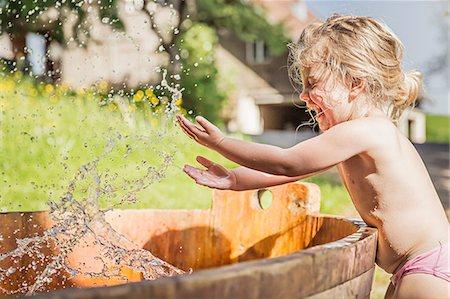 Female toddler splashing hands in water barrel Stock Photo - Premium Royalty-Free, Code: 649-07520340
