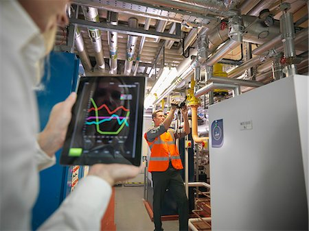 Office workers using digital tablet and camera to check efficiency of office heating in boiler room Stock Photo - Premium Royalty-Free, Code: 649-07520365