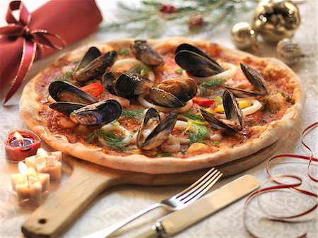 delicious - Homemade seafood pizza topped with calamari, prawns and mussels with festive decorations Stock Photo - Premium Royalty-Free, Code: 649-07520367