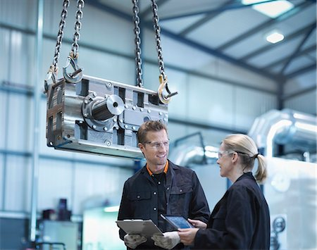 Engineers discuss plans on digital tablet in engineering factory Stock Photo - Premium Royalty-Free, Code: 649-07520457