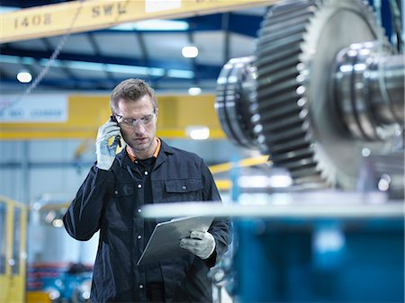 Engineer using mobile phone in engineering factory Stock Photo - Premium Royalty-Free, Code: 649-07520469