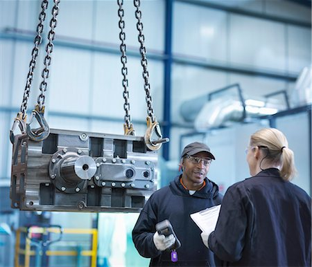 Engineers in discussion next to industrial gearbox in engineering factory Stock Photo - Premium Royalty-Free, Code: 649-07520460