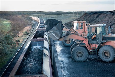 people working coal mines - Diggers loading coal onto train at surface coal mine at dawn Stock Photo - Premium Royalty-Free, Code: 649-07520486