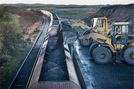 people working coal mines - Diggers loading coal onto train at surface coal mine at dawn Stock Photo - Premium Royalty-Free, Code: 649-07520487