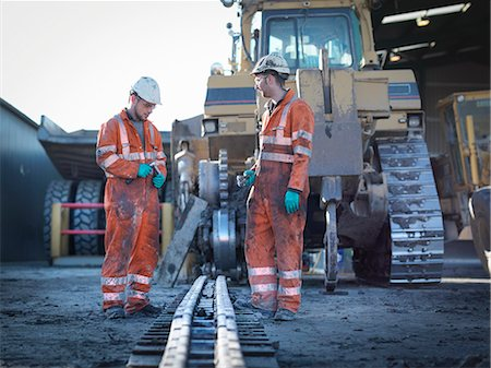 Apprentice and engineer work on machinery in surface coal mine Stock Photo - Premium Royalty-Free, Code: 649-07520495