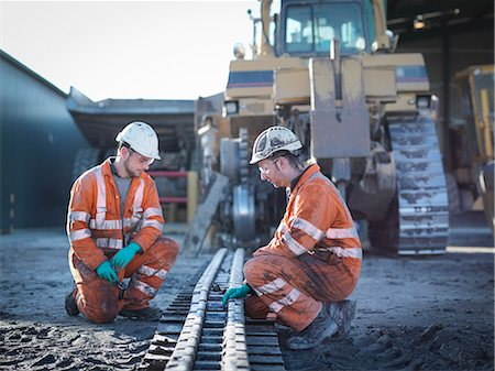 Apprentice and engineer work on machinery in surface coal mine Stock Photo - Premium Royalty-Free, Code: 649-07520496