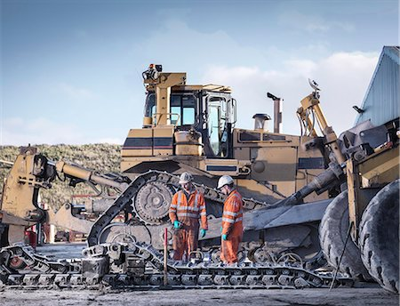 Apprentice and engineer work on machinery in surface coal mine Stock Photo - Premium Royalty-Free, Code: 649-07520493