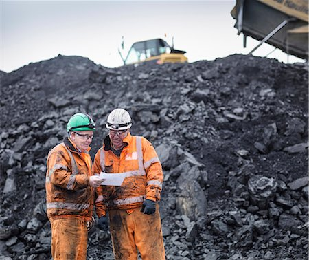 people working coal mines - Workers in discussion in front of coal stocks in surface coal mine Stock Photo - Premium Royalty-Free, Code: 649-07520511