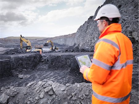 people working coal mines - Miner checks plans on digital tablet in surface coal mine Stock Photo - Premium Royalty-Free, Code: 649-07520528