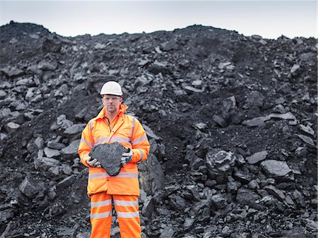 people working coal mines - Portrait of coal miner holding coal in surface coal mine Stock Photo - Premium Royalty-Free, Code: 649-07520536