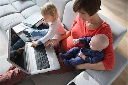 Mother, baby boy and female toddler using laptop on sofa Stock Photo - Premium Royalty-Free, Code: 649-07520605