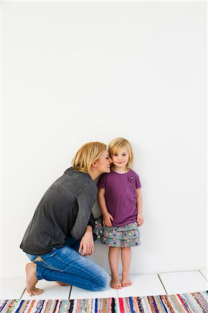 Studio shot of mother kneeling next to young daughter Stock Photo - Premium Royalty-Free, Code: 649-07520629