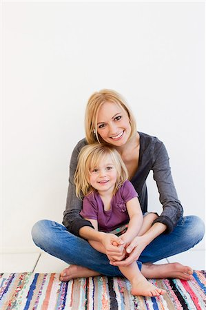 Studio portrait of mother and young daughter on rug Stock Photo - Premium Royalty-Free, Code: 649-07520636