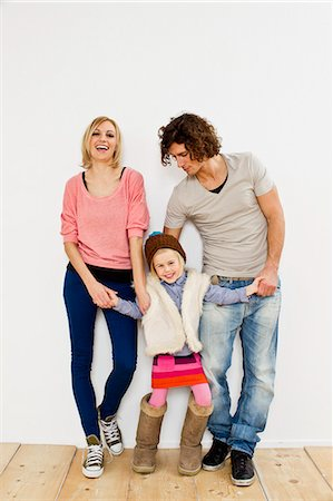 Studio shot of couple with young daughter wearing big boots Stock Photo - Premium Royalty-Free, Code: 649-07520655
