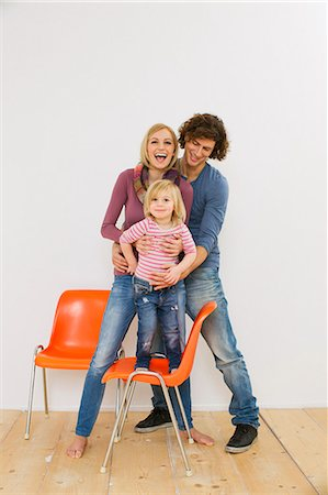 Studio shot of couple with young daughter standing on chair Stock Photo - Premium Royalty-Free, Code: 649-07520674