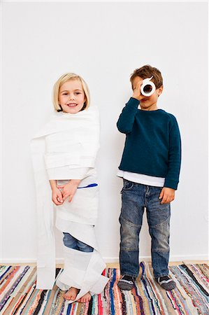 Studio shot of sister and brother with toilet rolls Stock Photo - Premium Royalty-Free, Code: 649-07520671