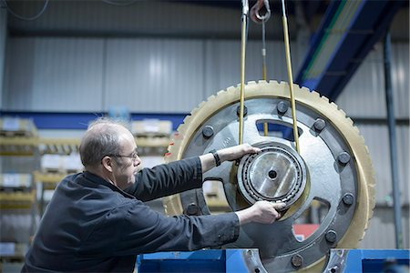 Engineer using crane to move large gear wheel in engineering factory Stock Photo - Premium Royalty-Free, Code: 649-07520710