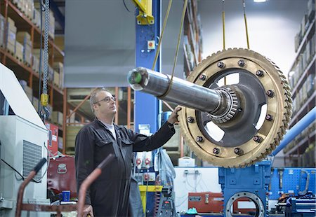 Engineer using crane to move large gear wheel in engineering factory Stock Photo - Premium Royalty-Free, Code: 649-07520711