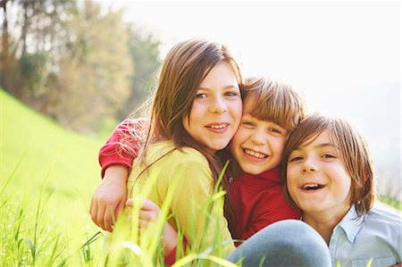 Sister and younger brothers sitting in grassy field Stock Photo - Premium Royalty-Free, Code: 649-07520758