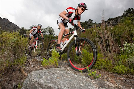 people mountain biking - Young couple riding mountain bikes on dirt track Stock Photo - Premium Royalty-Free, Code: 649-07520853
