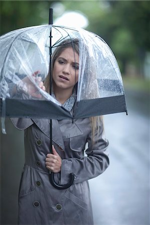people with umbrellas in the rain - Young woman looking at hole in umbrella Stock Photo - Premium Royalty-Free, Code: 649-07520864